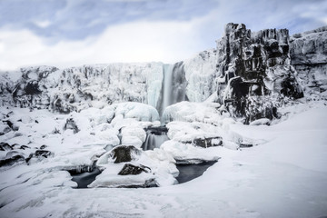 Waterfall pouring over icy cliffs, Iceland