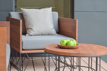 Apple tray on wooden top table next to wooden seat with outdoor cushion
