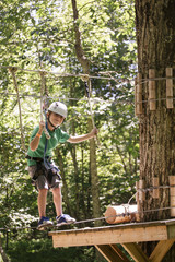 Caucasian boy balancing on slackline in forest