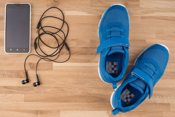 Flat lay shot of Sport equipment. Sneakers, earphones and phone