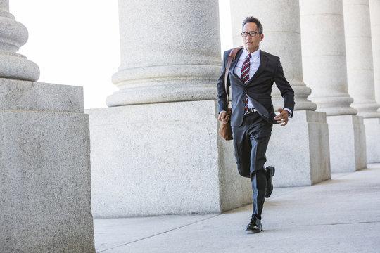 Mixed race businessman walking under columns