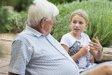 Grandfather and granddaughter talking in garden