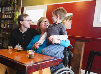 Paraplegic mother holding son in tea shop