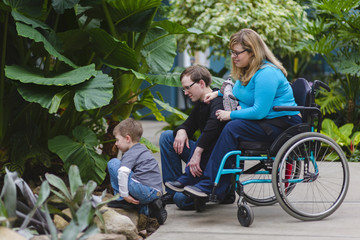 Paraplegic woman and family admiring plants