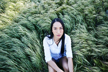Portrait of woman sitting in grass