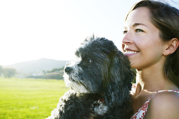 Caucasian woman holding dog outdoors
