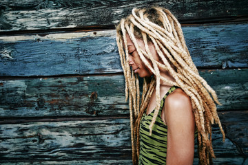 Woman with blonde dreadlocks at wooden wall