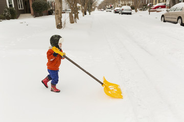 Small boy shoveling snow