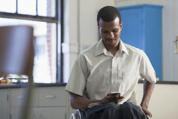 African American paraplegic man using cell phone