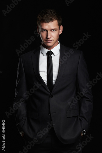27b8d1a19cc7 Businessman standing on black background.handsome young Man in suit ...