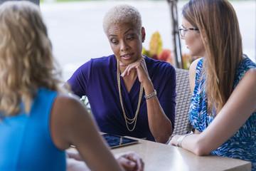 Businesswomen using digital tablet at table