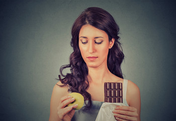 Confused looking woman with chocolate and apple trying to make a healthy choice