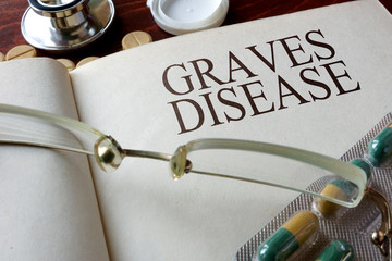 Book with diagnosis Graves disease and pills. Medical concept.