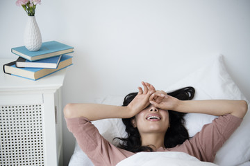 Hispanic woman waking up in bed
