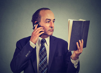 business man in suit, executive reading book talking on smart phone