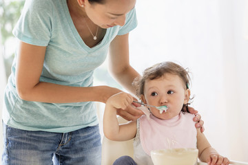 Mother spoon feeding her baby girl
