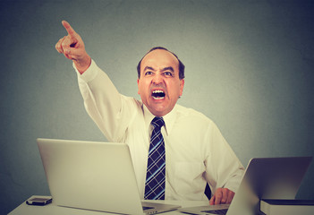Angry middle aged businessman sitting at his desk and screaming at his employees