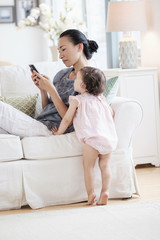 Mother and baby daughter using cell phone