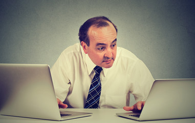Middle aged business man multitasking working on two computers in his office