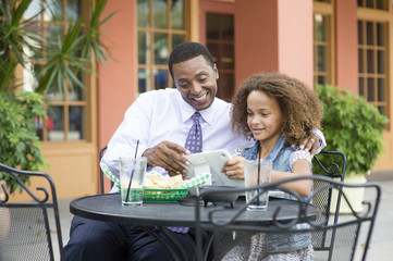 Father and daughter eating at outdoor restaurant table