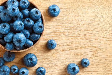 Healthy blueberries in bowl on wooden background. Close up, top view, high resolution product. Harvest Concept
