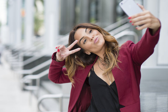 Hispanic businesswoman taking selfie outdoors