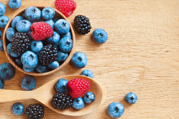 Heap of tasty berries on wooden table. Close up, top view, high resolution product. Harvest Concept