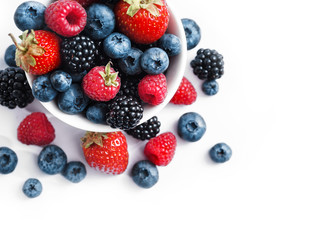 Ceramic bowl with blueberries, strawberries and blackberries on white background. Close up, high resolution product. Harvest Concept