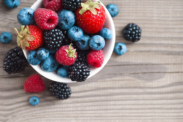 Mix of fresh berries in a basket on rustic wooden background. Close up, top view, high resolution product. Harvest Concept