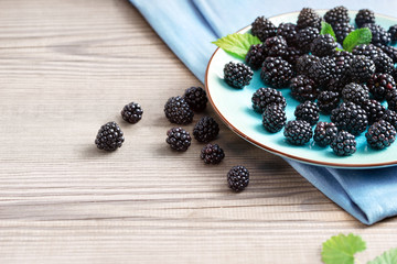 Ceramic plate with blackberries at old wooden table. Close up, high resolution product. Harvest Concept