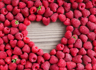 Heart shape made of premium raspberries on wooden background. Close up, top view, high resolution product. Harvest Concept