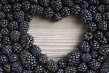 Heart shape made of premium Blackberries on wooden background. Close up, top view, high resolution product