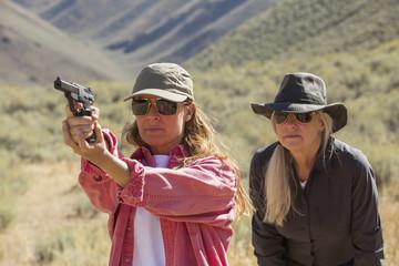 Caucasian women aiming gun outdoors