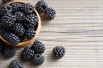 Fresh blackberries in bowl on wooden background. Close up, top view, high resolution product. Harvest Concept
