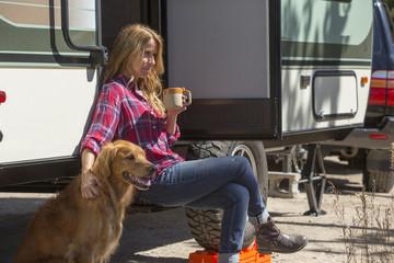 Caucasian woman petting dog at trailer