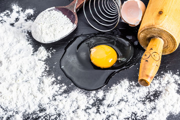Ingredients for baking - flour, egg, wooden spoon, egg beater, c