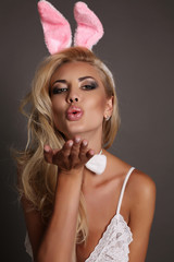 sexy blond girl with bunny ears head accessory, symbol of Easter holiday