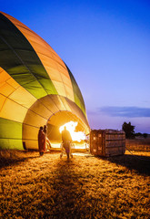 Hot air balloon inflating in rural field