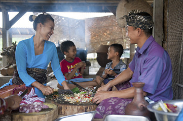 Asian family cooking together in outdoor kitchen