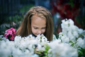 Caucasian girl smelling flowers in garden