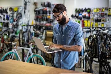 Bike mechanic checking at laptop