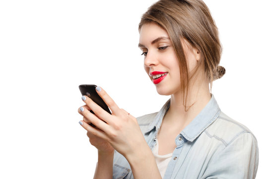 beautiful young woman chatting sms or serfing the internet by mobile phone, on a white background