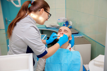 Nice adult guy on checking teeth in dental office