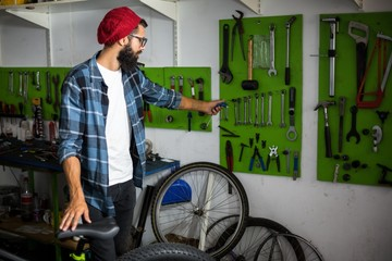 Bike mechanic picking up tools to repair a bicycle