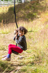 Young girl riding a zip-line, grassy playground warm summers day.