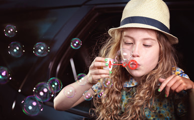 Blonde hair young girl lets soap bubbles in car