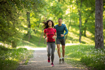 Young couple jogging at the woods.Green environment.