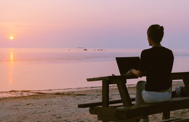 Young woman sitting at the table with a laptop in front of sunset view. Lady frelanser working at the beach.