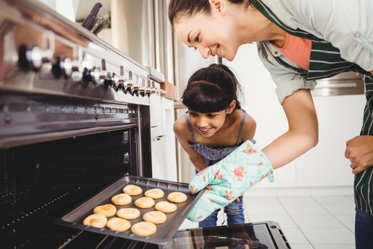 Mother and daughter placing cookies in oven