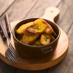 Fried slices of the ripe plantain in bowl, which can be eaten as snack or is used to accompany dishes in some South American countries (Selective Focus, Focus on the front of the upper plantain slice)